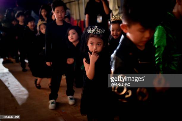 A model reacts as she waits to present a creation from the Sun Haitao collection during China Fashion Week in Beijing on March 30 2018 / AFP PHOTO /...