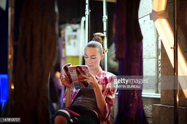 Model reads a magazine in the backstage of French designer Julien Fournie during the Haute Couture Fall-Winter 2012-2013 shows on July 3, 2012 in...