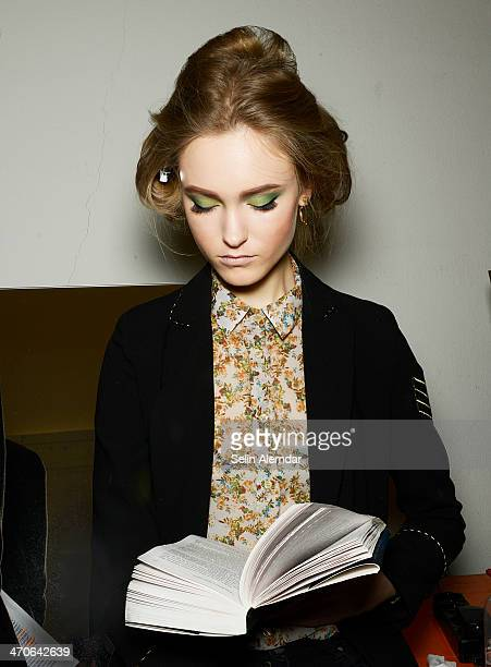 Model reads backstage ahead of Andrea Incontri show during Milan Fashion Week Womenswear Autumn/Winter 2014 on February 20, 2014 in Milan, Italy.