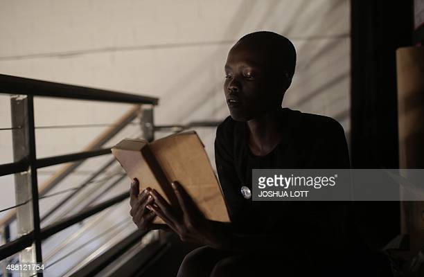 A model reads her book backstage before presenting a creation by Thakoon during his Spring/Summer 2016 collection at New York Fashion Week in New...