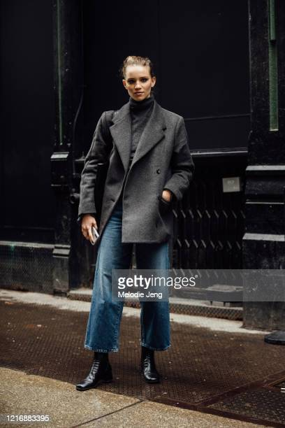 Model Rebecca Leigh Longendyke wears a boxy gray peacoat, blue jeans, and black boots after the Khaite show on February 11, 2020 in New York City.