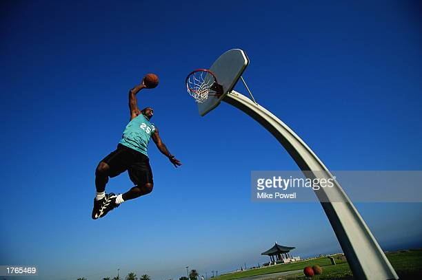 Basketball man jumping to put ball in net low angle view