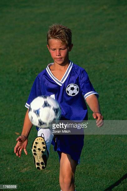 Boy playing soccer kicking ball