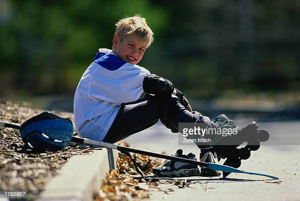 Boy wearing inline skates sitting on kerb portrait