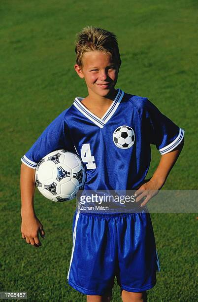 Boy wearing soccer kit holding ball portrait