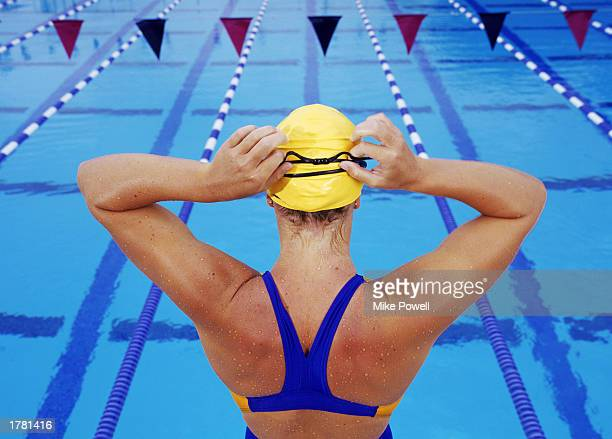 Female competitive swimmer adjusting goggles over swim cap rear view