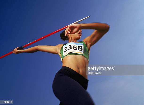 Female competitor about to throw javelin, low angle view.