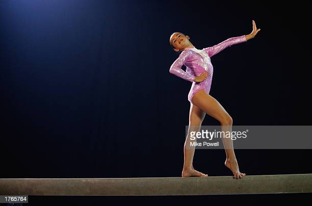 Female gymnast performing routine on balance beam