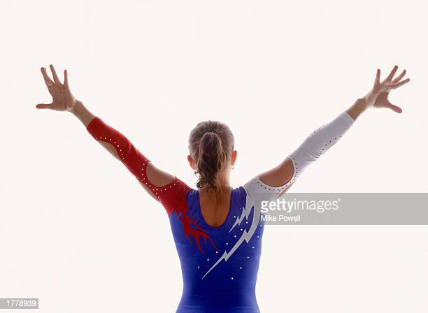 Female gymnast with arms outstretched rear view