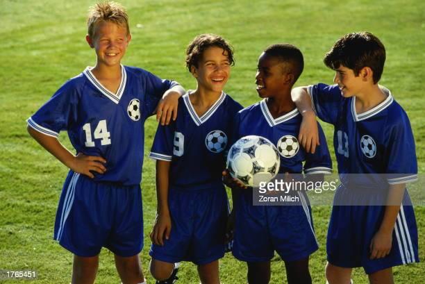 Four boys wearing soccer kit holding ball