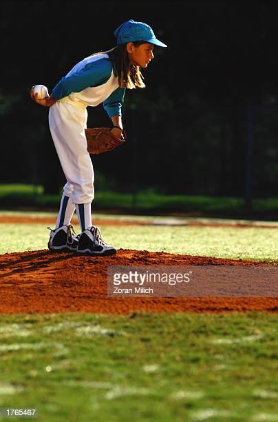 Girl playing baseball, standing on pitcher''s mound