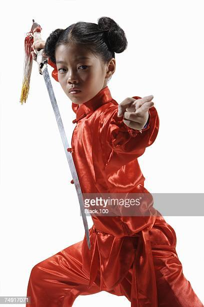 Girl with sword practicing wushu pointing looking away