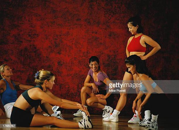 Group of young women relaxing and stretching in gym