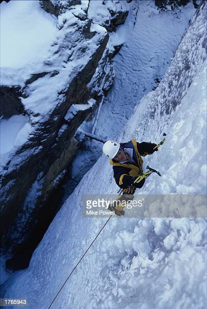 Ice climber using iceaxes ascending crevasse elevated view