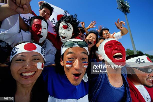 Japanese soccer fans with painted faces cheering in stands