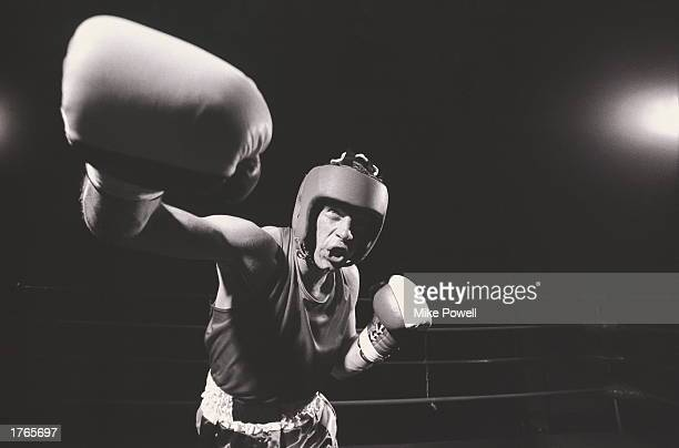 Male boxer in ring throwing punch low angle view