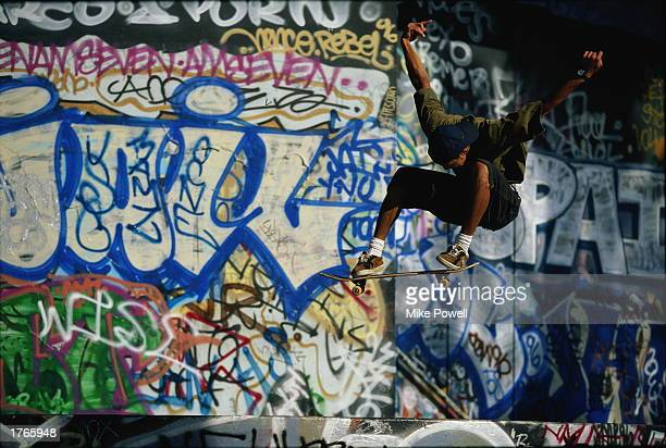 Male skateboarder in midair graffiticovered wall in background
