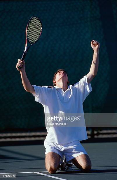 Male tennis player kneeling on court with arms raised