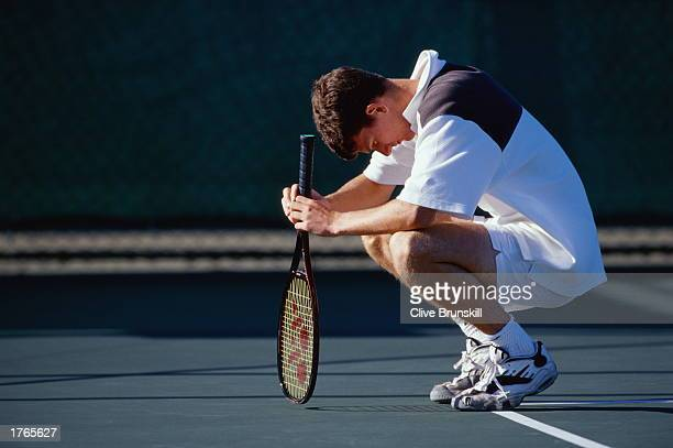 Male tennis player resting at edge of court