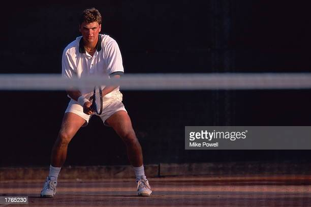 Male tennis player standing on court view across net