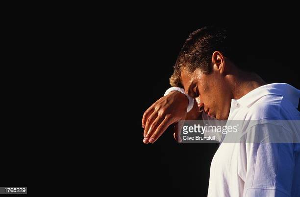 Male tennis player wiping forehead with sweatband closeup