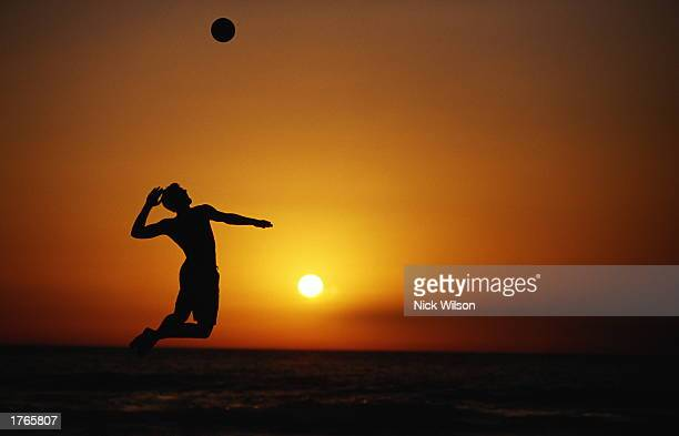 Male volleyball player jumping to hit ball silhouetted at sunset
