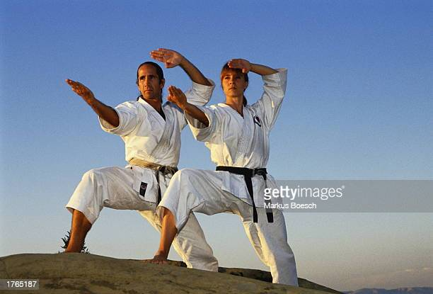Man and woman practising karate outdoors low angle view