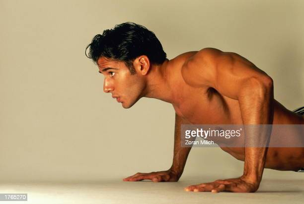 Muscular young man doing pushups closeup