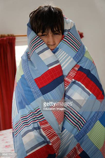 Model released portrait of sleepy boy standing wrapped in his duvet
