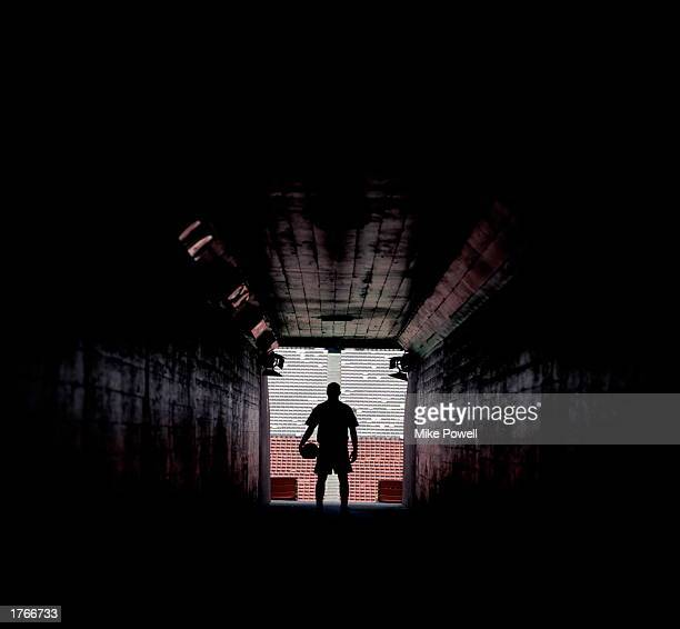 Silhouette of soccer player standing at end of stadium tunnel