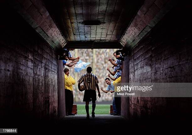 Soccer player walking through tunnel entrance to stadium