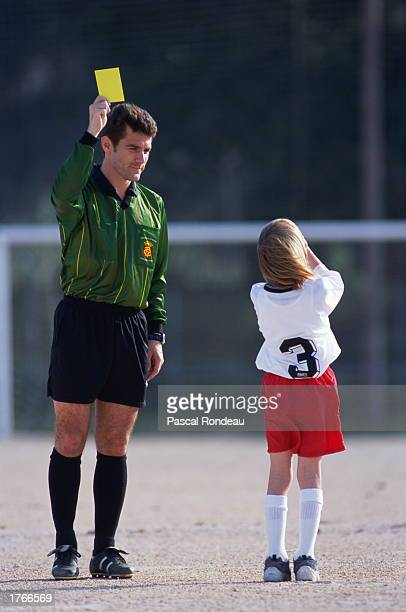 Soccer referee holding yellow card boy covering face rear view