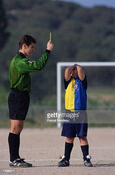 Soccer referee holding yellow card boy with hands on face