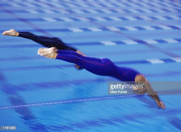 Two female swimmers diving off of starting blocks at beginning of race