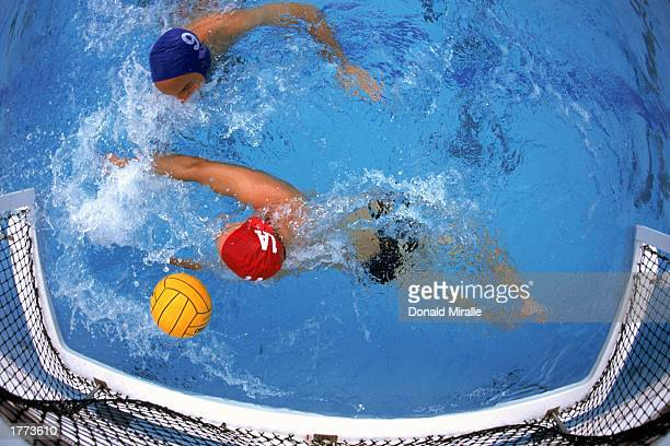 Water polo player shooting ball past defender into goal, overhead view.