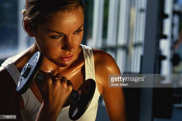 Woman exercising with weights in gym, close-up