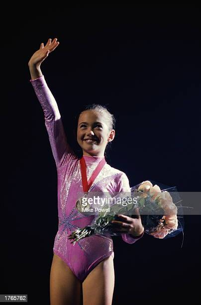 Young female gymnast wearing medal around neck holding bouquet