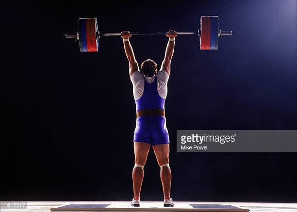 Competitive male weightlifter holding barbell over head rear view