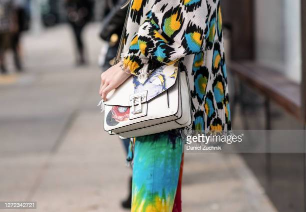 Model Remington Williams is seen wearing an animal print sweater, tie dye pants and white printed bag outside the Jason Wu show during New York...