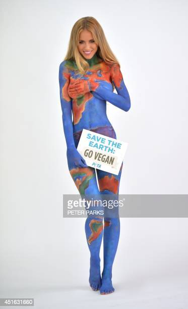 Model Renee Somerfield poses after having her body painted as the earth with a sign reading Save the Earth Go Vegan for a new advertisement by People...