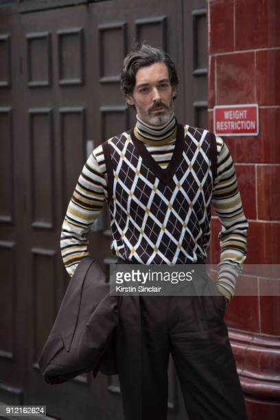 Model Richard Biedul wears a Daks London sleeveless sweater and roll neck sweater Chester Barrie brown suit day 3 of London Mens Fashion Week...