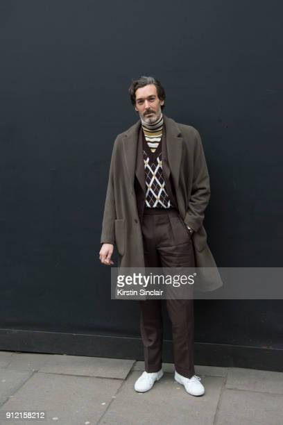 Model Richard Biedul wears a Reiss coat Daks London sleeveless sweater and roll neck sweater Chester Barrie brown suit day 3 of London Mens Fashion...