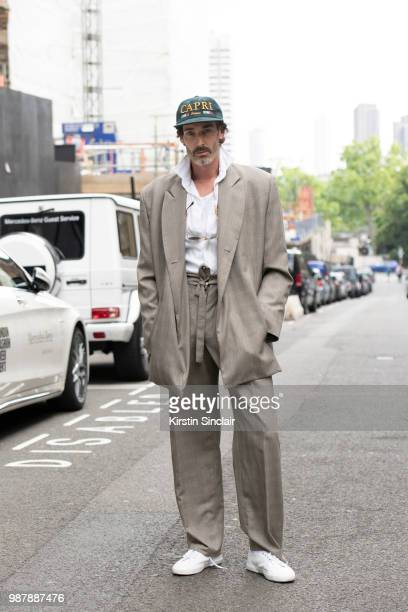 Model Richard Biedul wears an Alex Mullins suit and Palce skateboards cap and Superga trainers during London Fashion Week Men's on June 10 2018 in...