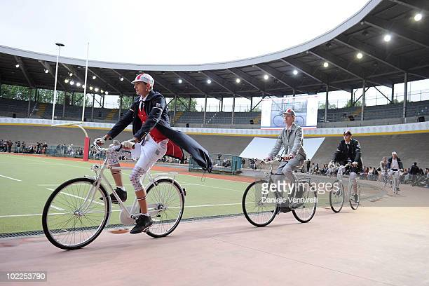 A model rides by bike the runway in the Moncler Gamme Bleu show during Milan Fashion Week for Menswear Spring/Summer 2011 on June 20 2010 in Milan...