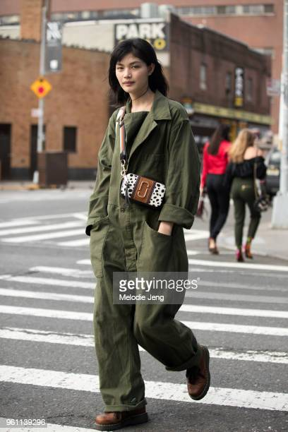 Model Rina Fukushi wears a green jumpsuit and a Marc Jacobs camera paperclip bag during New York Fashion Week Spring/Summer 2018 on September 9 2017...