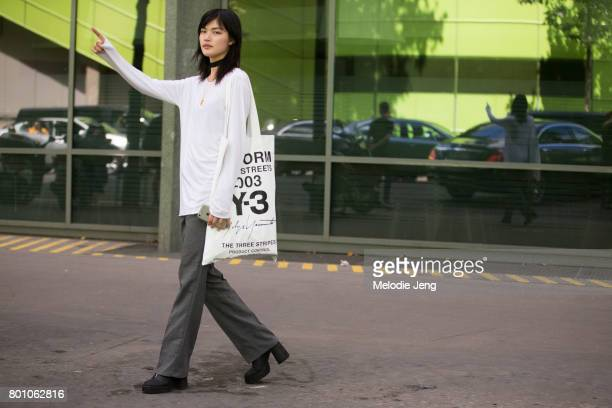 Model Rina Fukushi wears a Y3 bag outside the Y/3 show on June 25 2017 in Paris France