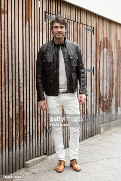 Model Robert Konjic wears a Belstaff jacket with white jeans cream jumper and tan brogues during London Fashion Week Men's June 2019 on June 09 2019...