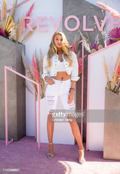Model Romee Strijd is seen wearing white cropped jacket denim jeans shorts cropped top at Revolve Festival during Coachella Festival on April 13 2019...