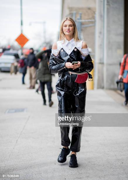 Model Romee Strijd wearing black vinyl overall Miu Miu belt bag white button shirt seen outside Ralph Lauren on February 12 2018 in New York City
