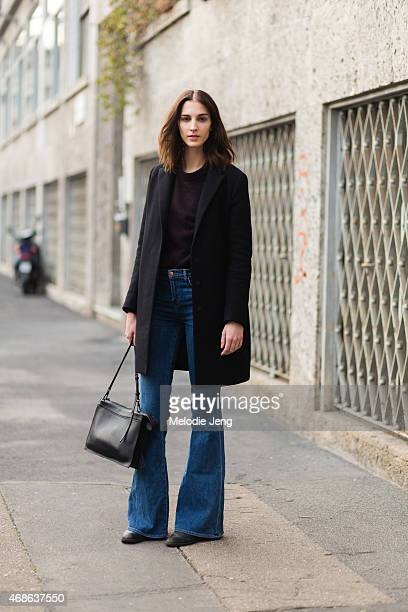 Model Ros Georgiou exits the Marco de Vincenzo show in an COS jacket Other Stories sweater J Brand jeans and a Phillip Lim bag on Day 3 of Milan...